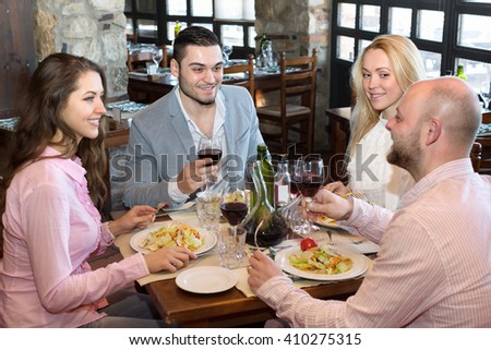 Two happy married couple sitting at restaurant table
