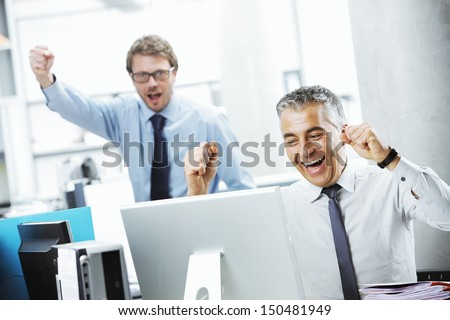 Two happy mature businessman celebrating their success - stock photo