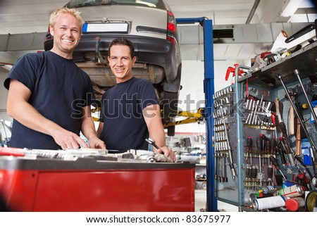 Two happy mechanics standing in garage - stock photo