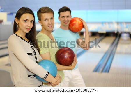 Two happy men and girl smile and hold balls in bowling club; focus on woman; shallow depth of field - stock photo