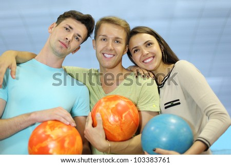 Two happy men and woman embrace and hold orange and blue balls in bowling club; shallow depth of field - stock photo
