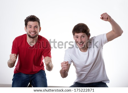 Two happy men cheering because of a victory - stock photo
