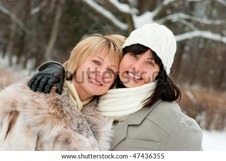 Two happy middle-aged women in winter nature