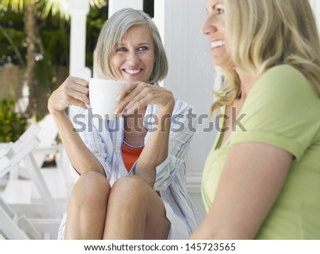 Two happy middle aged women sitting on verandah with coffee cup - stock photo