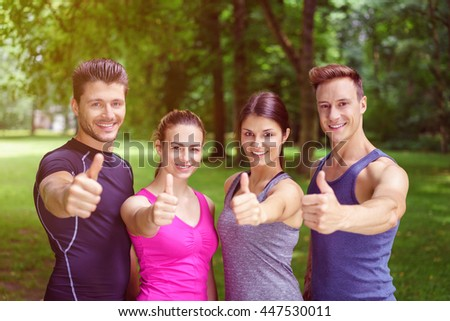 Two happy motivated fit young couples giving a thumbs up of approval and success and they pose in their sportswear in a park smiling at the camera