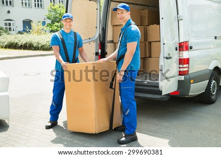 Two Happy Movers In Blue Uniform Loading Boxes In Truck - stock photo