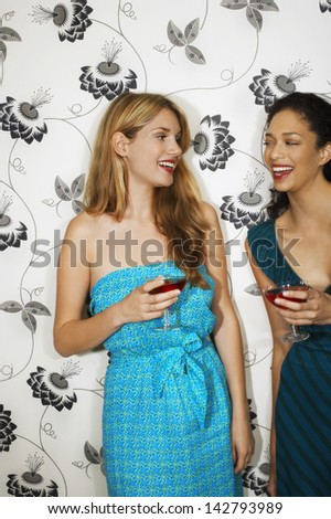 Two happy multiethnic young women drinking martinis against floral print wall - stock photo