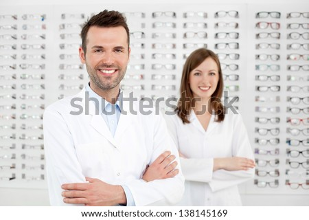 Two happy opticians optometrists standing in optician store. - stock photo