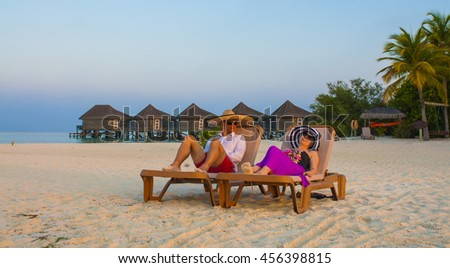 Two happy people relaxing on the beach, sitting down on comfortable sunbed and taking sunbath, rear view, summer holidays concept - stock photo
