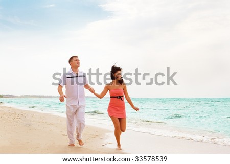 Two happy people running along the coastline
