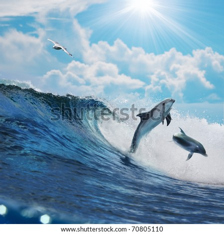 Two happy playful dolphins leaping from ocean breaking surfing wave to foam in front of cloudy seascape - stock photo