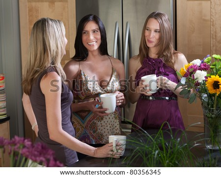 Two happy pregnant women at different points in their pregnancy enjoy a cup of coffee with friend - stock photo
