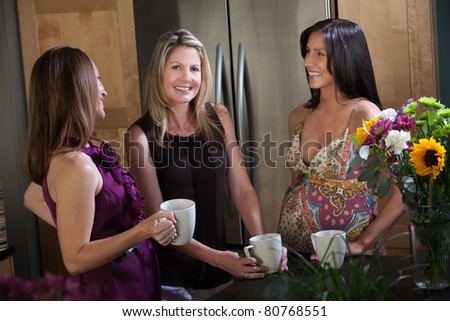 Two happy pregnant women at different points in their pregnancy enjoys a cup of coffee or tea with friend in kitchen