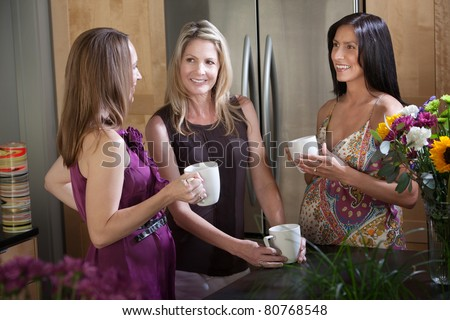 Two happy pregnant women with friend in a kitchen - stock photo