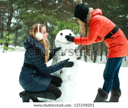 Two happy pretty girls building a snowman in pinewood on a winter day - stock photo