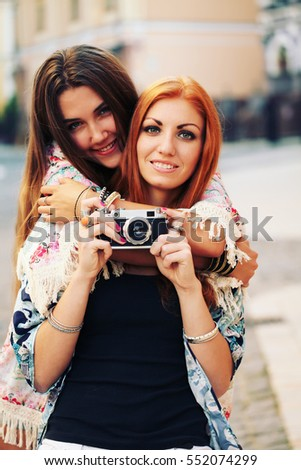 Two happy pretty young best friends, hugs smiling laughing and having funny crazy time together, wearing stylish retro vintage feminine clothes. Outdoors.