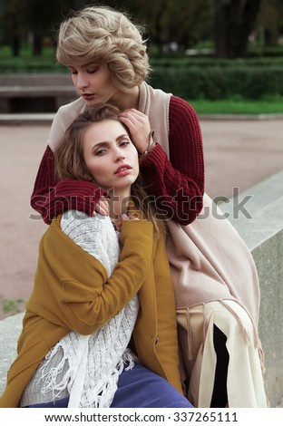 Two happy pretty young women, fashion shooting. Outdoors. - stock photo