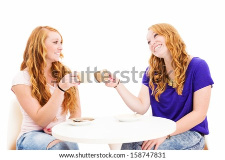two happy redhead women clink glasses with coffee cups on white background - stock photo