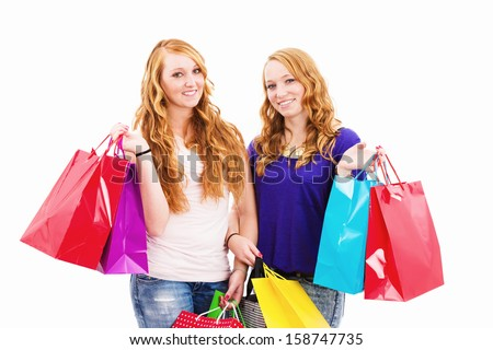 two happy redhead women with shopping bags on white background - stock photo
