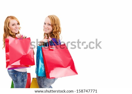 two happy redhead women with shopping bags turning around on white background - stock photo