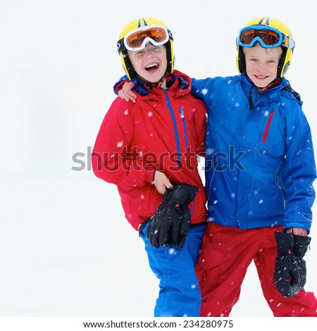 Two happy school boys, twin brothers in colorful snowsuits, having fun skiing in alpine mountains during snowy winter vacation
