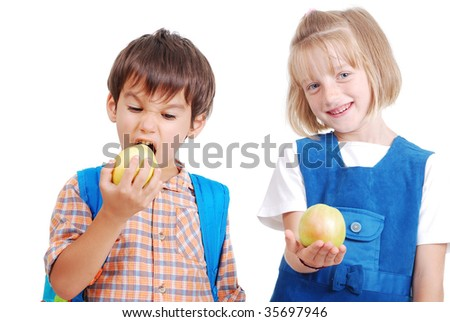 Two happy school children eating an apple - stock photo
