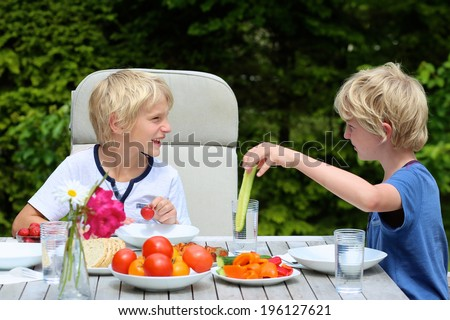 Two happy schoolboys, twin brother, laughing and having healthy lunch or dinner outside sitting at picnic table in the garden at the backyard of the house on a sunny summer day - stock photo