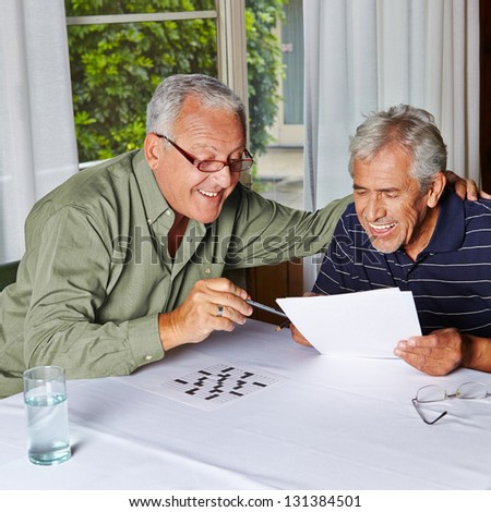 Two happy senior citizens solving riddles in a rest home - stock photo