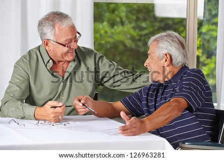 Two happy senior men solving crossword puzzle in a rest home - stock photo