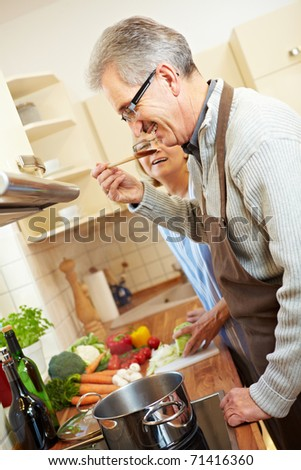 Two happy senior people cooking in the kitchen - stock photo