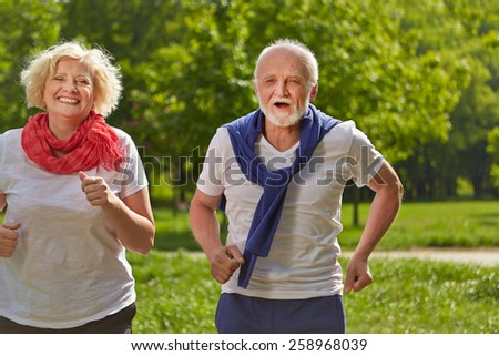 Two happy senior people jogging in a park in summer - stock photo