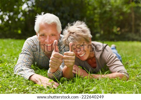 Two happy senior people laying in a meadow holding their thumbs up - stock photo
