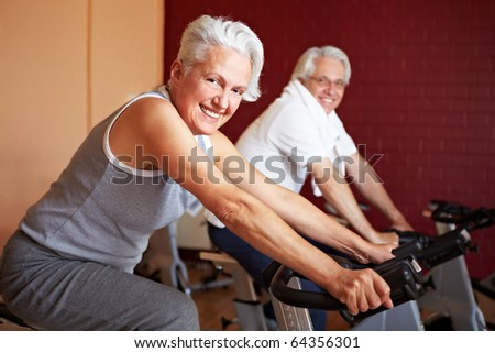 Two happy senior people on bikes in gym - stock photo