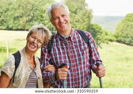 Two happy senior people smiling in summer while hiking in nature - stock photo