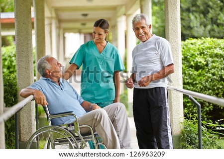Two happy senior people taking to a nurse in a nursing home - stock photo