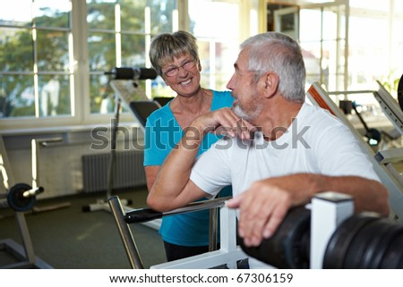 Two happy senior people talking in gym - stock photo