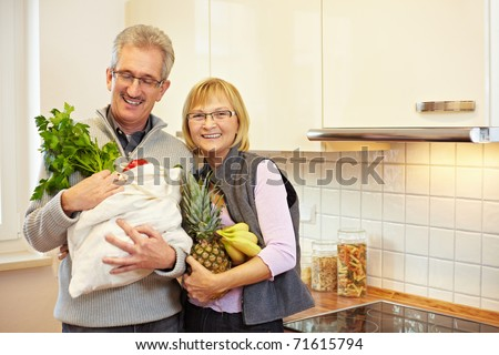 Two happy senior people with groceries in the kitchen