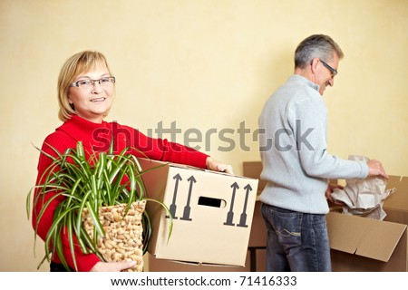 Two happy senior people with many moving boxes - stock photo