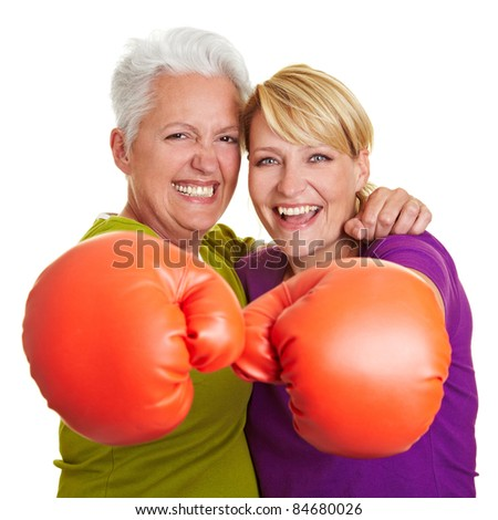 Two happy senior women boxing with red boxing gloves