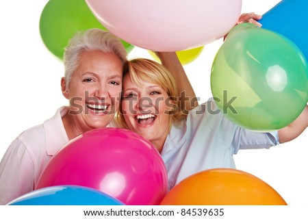 Two happy senior women cheering with many balloons - stock photo