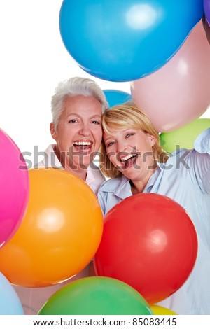 Two happy senior women cheering with many balloons - stock photo