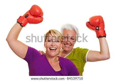 Two happy senior women cheering with red boxing gloves