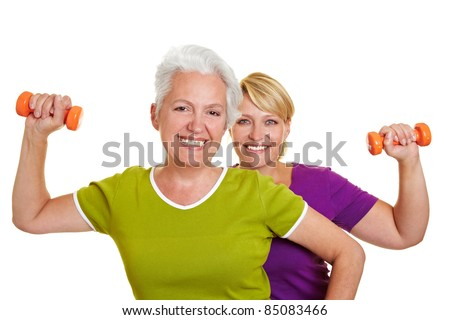 Two happy senior women doing fitness training with dumbbells