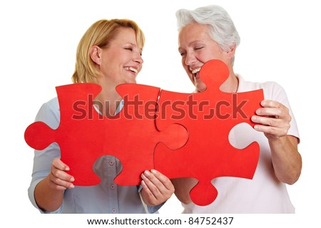 Two happy senior women holding jigsaw puzzle pieces - stock photo