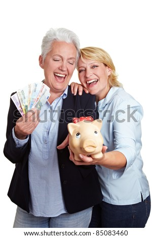 Two happy senior women with money and piggy bank - stock photo