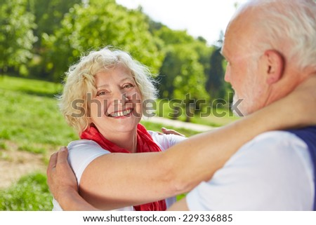 Two happy seniors in love dancing together in nature in summer - stock photo