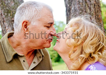 Two happy seniors kissing and having fun together.