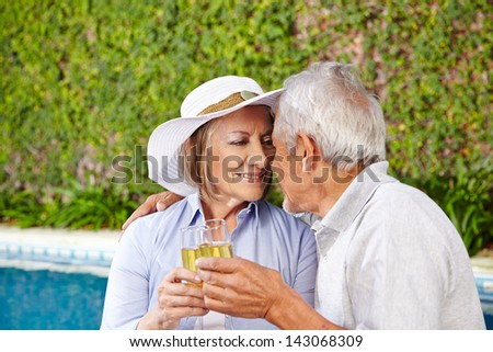 Two happy seniors sitting with champagne at pool in holiday