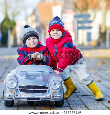 Two happy sibling boys in red jackets and rain boots playing with big old toy car, outdoors.  Kids leisure on cold day in winter, autumn or spring. - stock photo