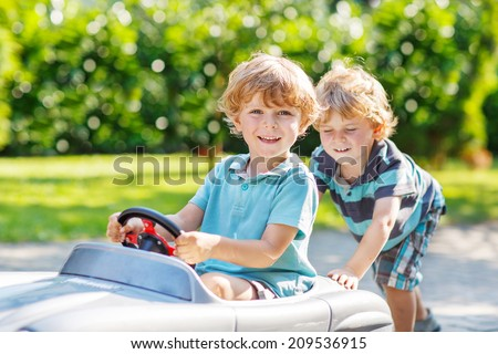 Two happy sibling boys playing with big old toy car in summer garden, outdoors. Selective focus on child in car. - stock photo